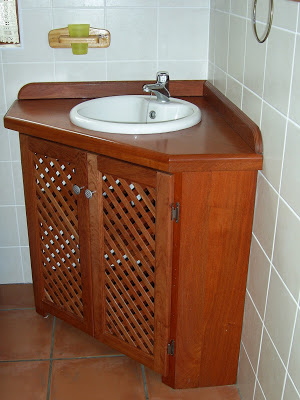 Wash basin cabinet built into the corner of the bathroom. Made of rosewood and with louver doors