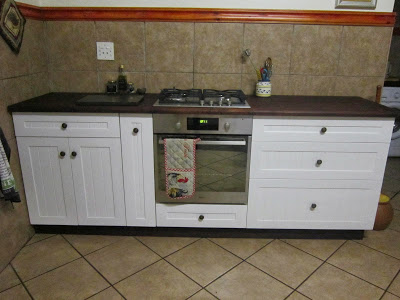 The farm style stove cupboard has a built-in gas stove and electric oven. Note the narrow spice drawer and the large drawers for pots and pans