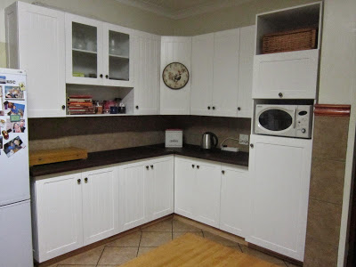 The doors of the farm style kitchen cupboards are made of supawood sprayed with white paint. The top and base are made of laminated stained saligna