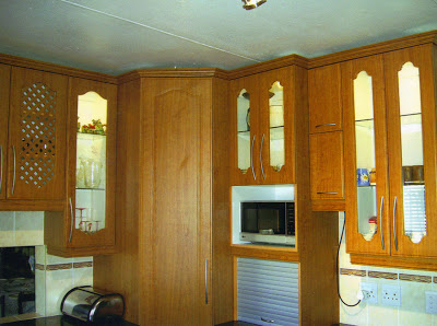 """Kitchen cupboards made of durable, synthetic material (""""wraps"""") which gives a serviceable finish and is easy to clean. Take notice of the tall built-in groceries cupboard, as well as the silver-coloured roll-up door where you can store your bread-board, toaster, kettle, etc"""