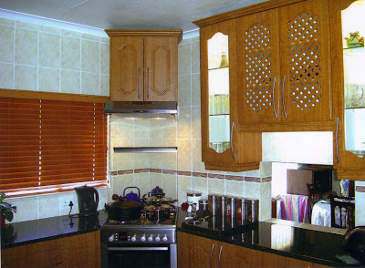 The lit up cupboards with glass and louver doors give an interesting variation to the solid doors. The crown mouldings on top give a fine finish to the cupboards. The extractor which absorbs the smell of the food from the stove is fitted beneath the cupboard in the corner