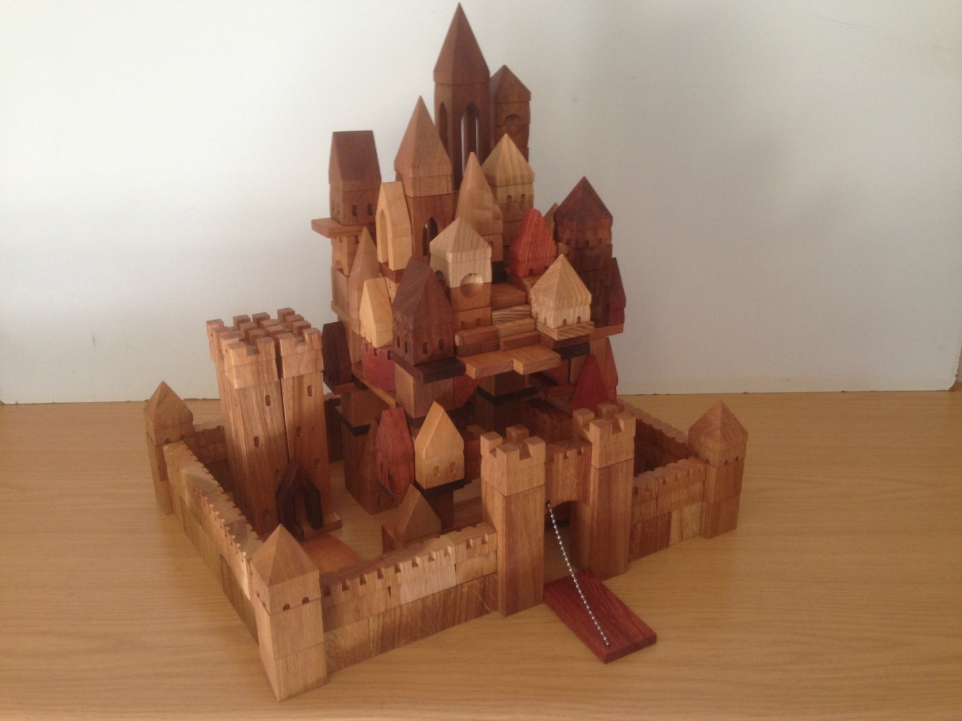 Walled Medieval city with drawbridge. Wooden blocks are made of hard and precious woods. Blocks for city: 130 pieces. Wall with drawbridge: 75 pieces