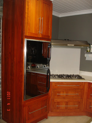 The gas stove and eye-high oven in rosewood cupboards